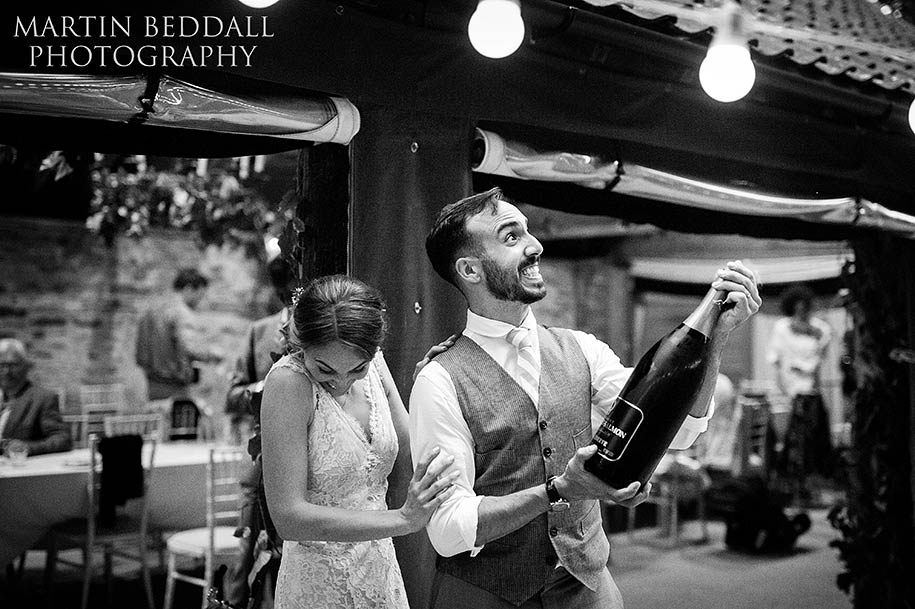Bride and groom opening up a Jeroboam