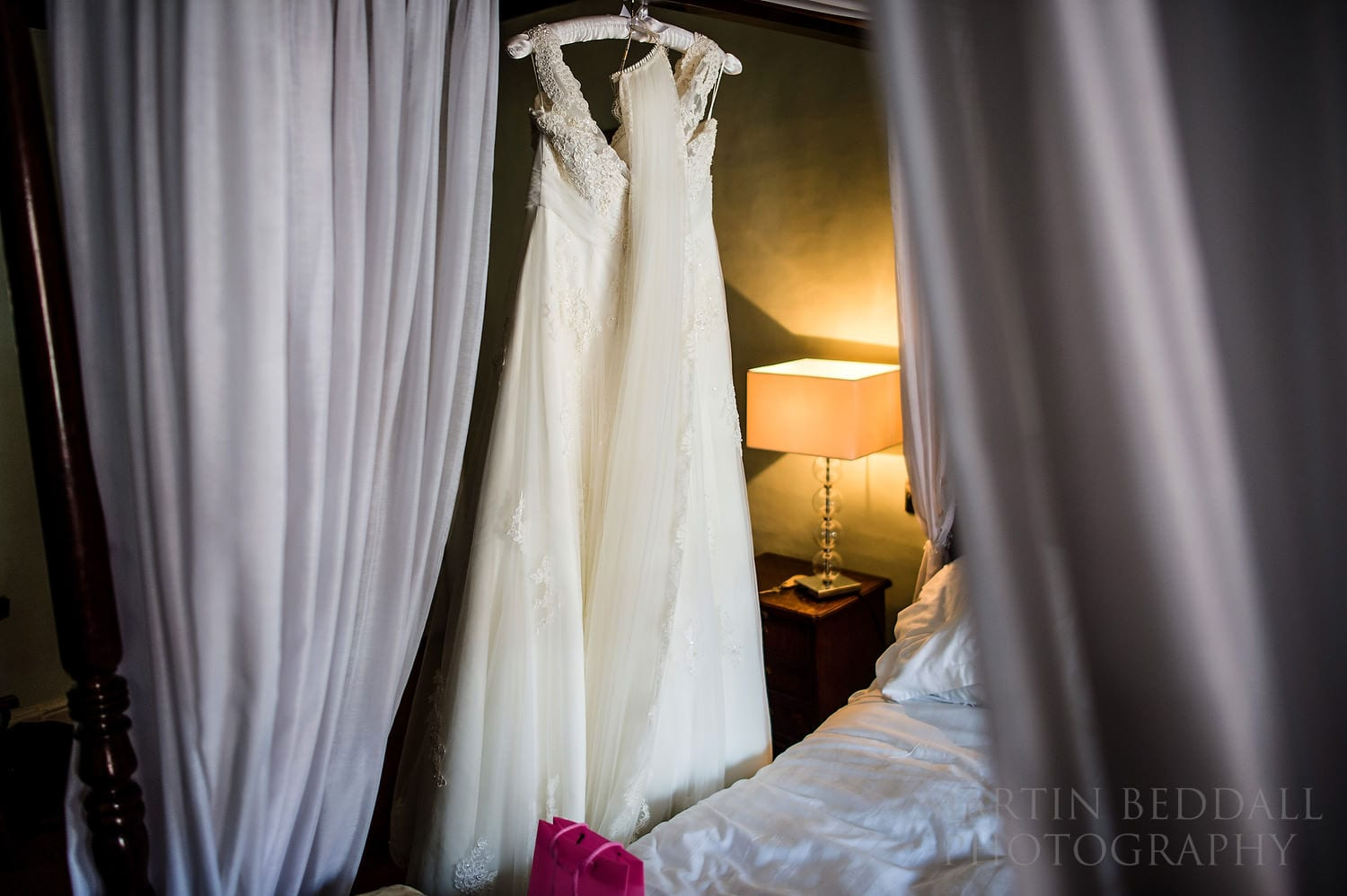 Wedding dress hanging on the four poster bed
