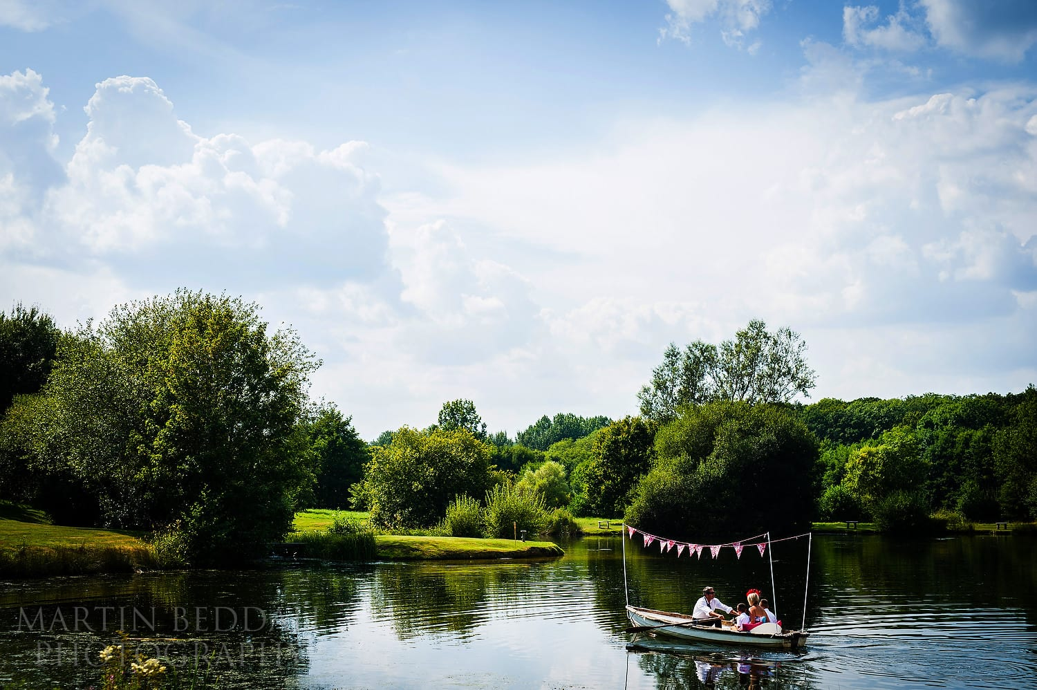 Wedding guests rowed on a small boat at Duncton Mill wedding reception