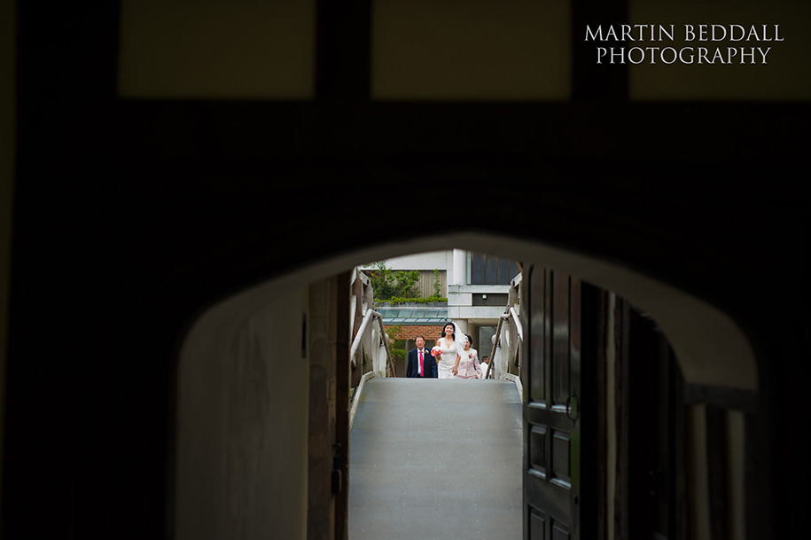 Bride crosses the mathematical bridge with her parents at Queens' college Cambridge