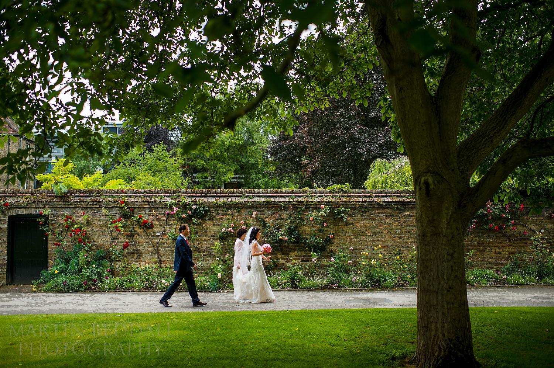 Bride walks with her parents to Queens' College chapel