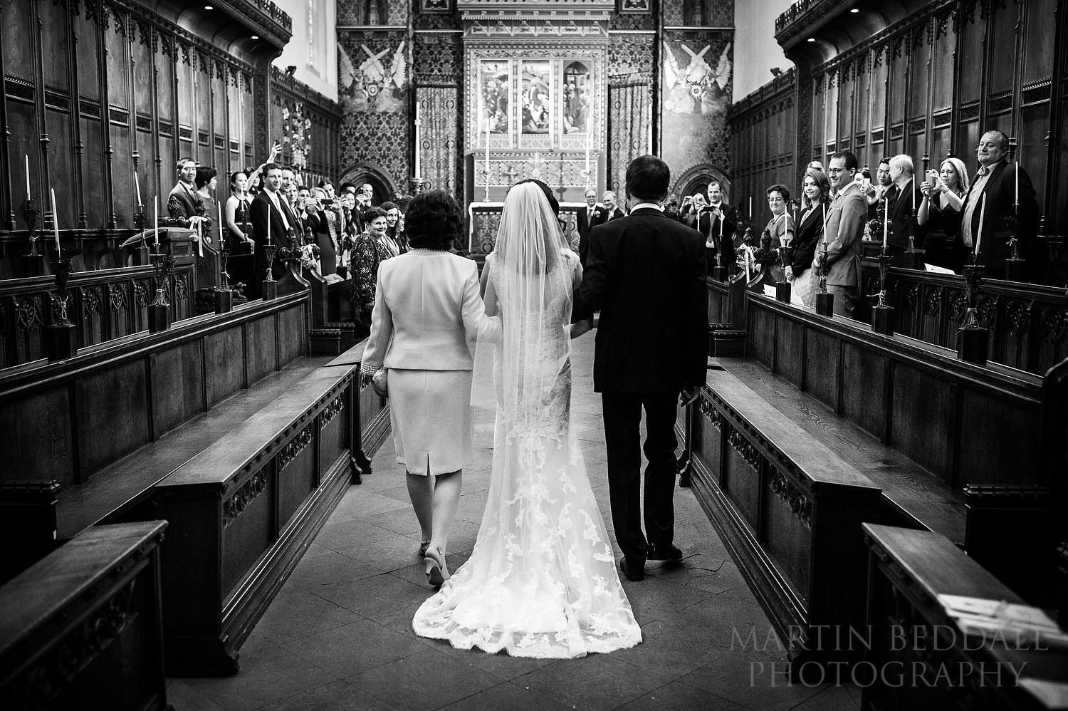 Bride walks down the aisle wiuth her parenst at Queens' College chapel