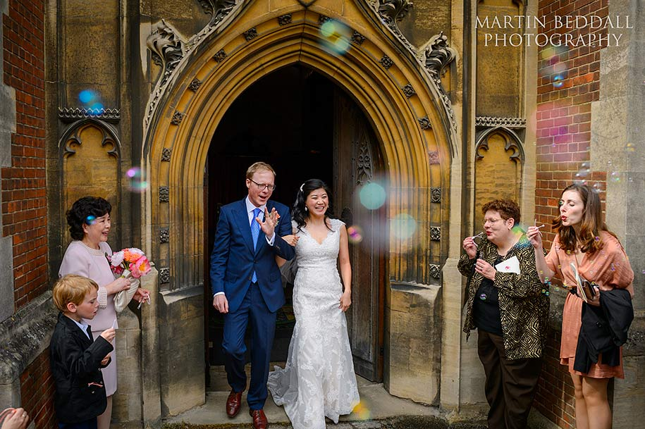 Bride and groom exit Queens' college chapel to bubbles