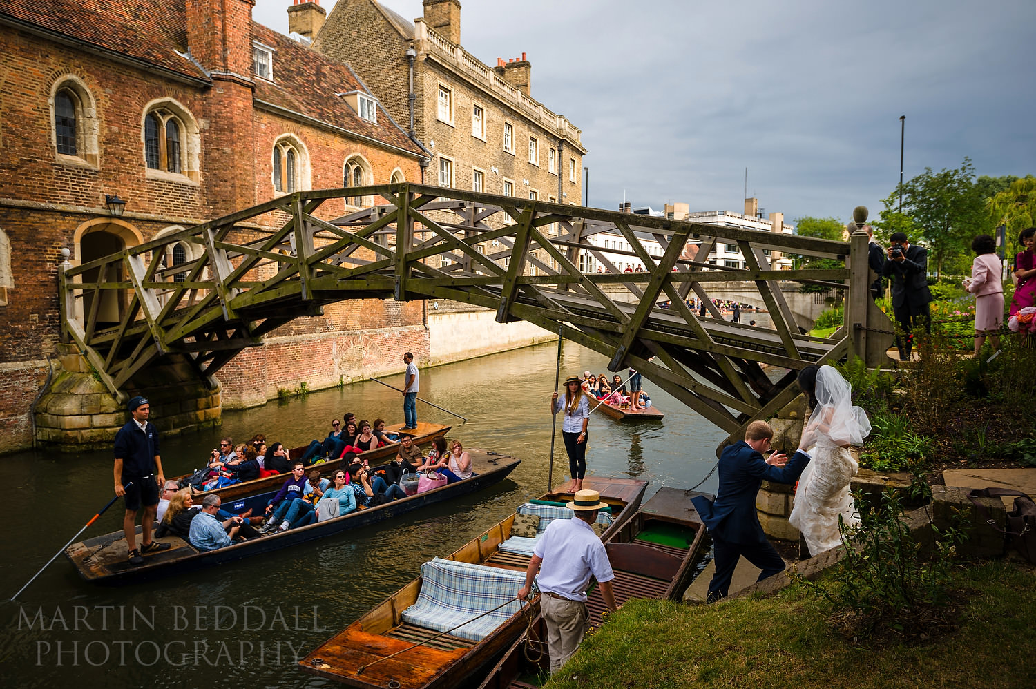 Bride and groom get onto a punt at Queens' College wedding