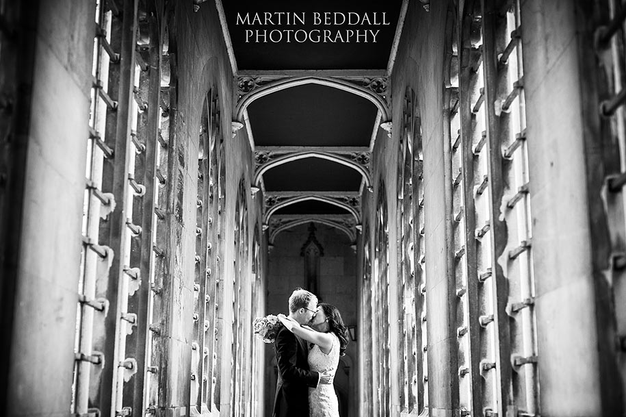 Bride and groom kiss on the bridge of Sighs at St John's college Cambridge