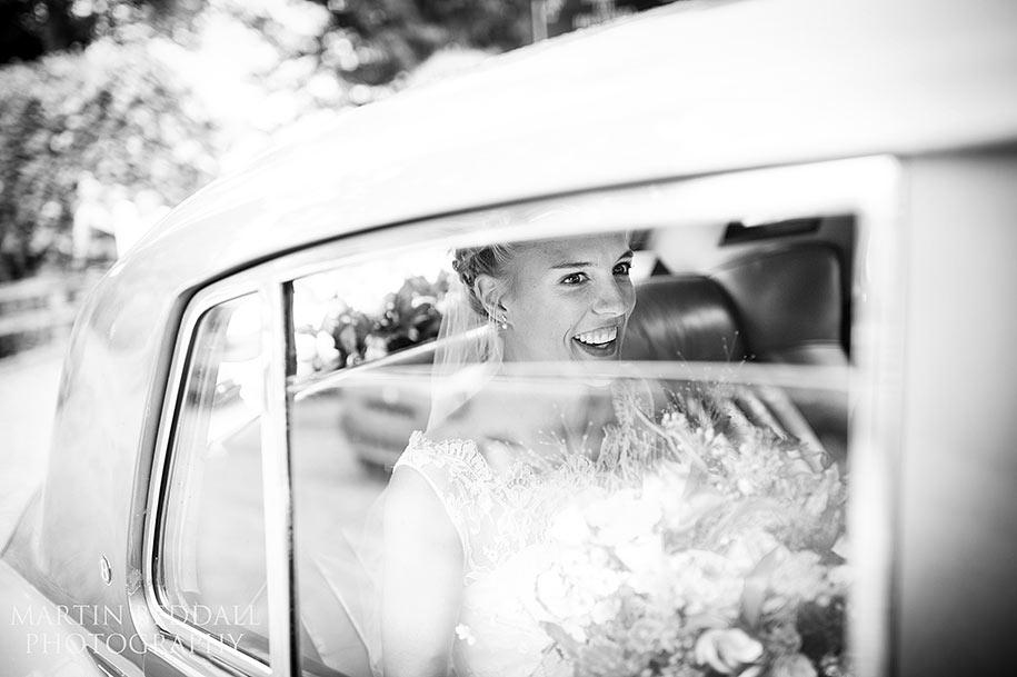 Smiling bride in the wedding car