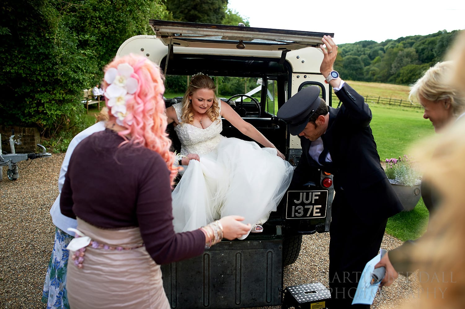 Bride arrives by chaffeur driven Land Rover