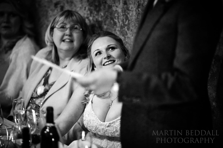 Bride smiling at the groom as he speaks