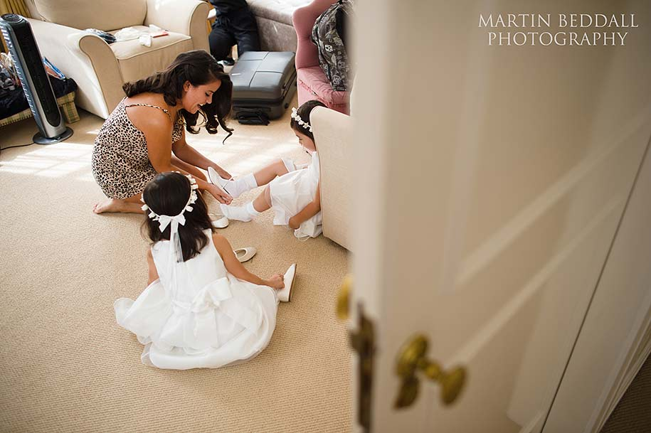 Bride helps the flowergirls get dressed