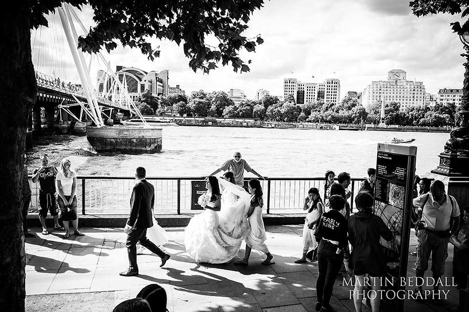 Bridal party walk along the South Bank