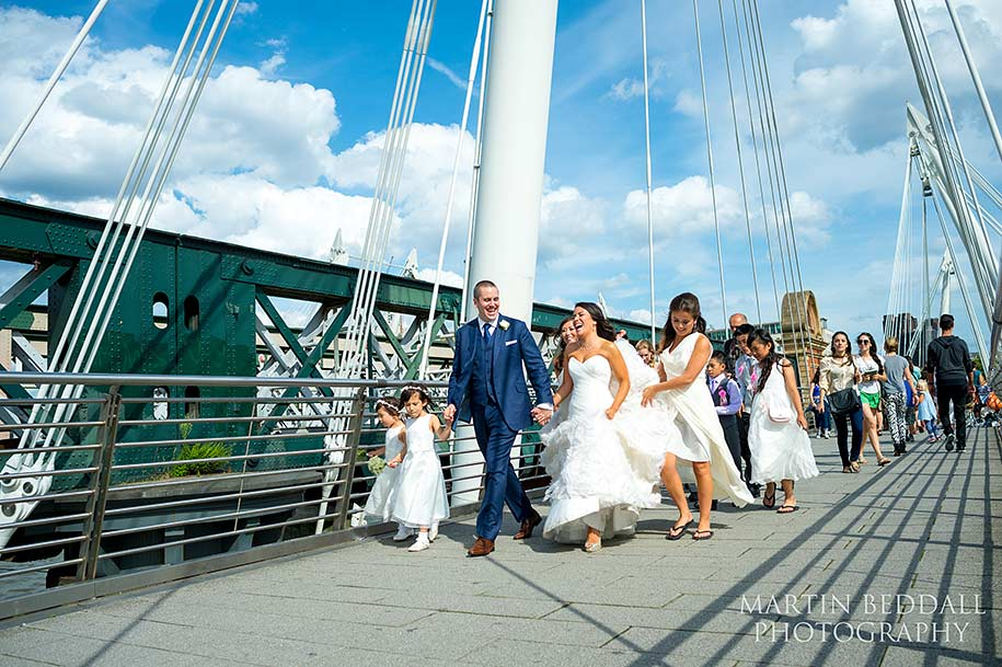Bridal party walk across Hungerford Bridge