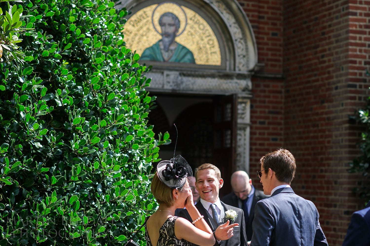Groom laughing with wedding guests outside the church in Haywards Heath