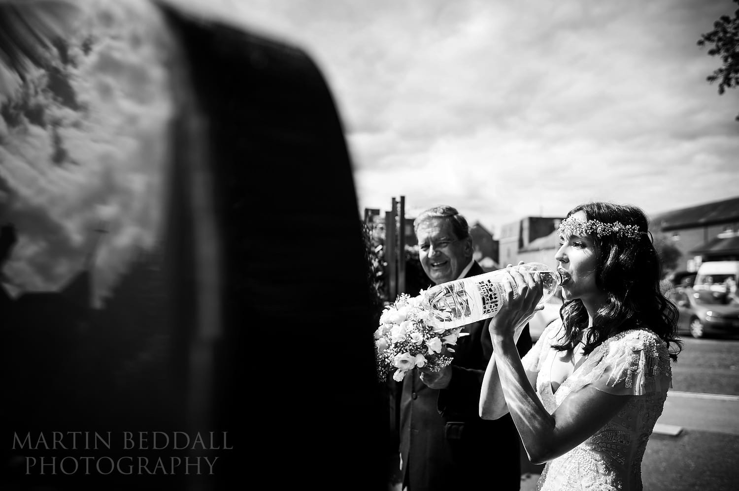 Bride takes a swig from the water bottle