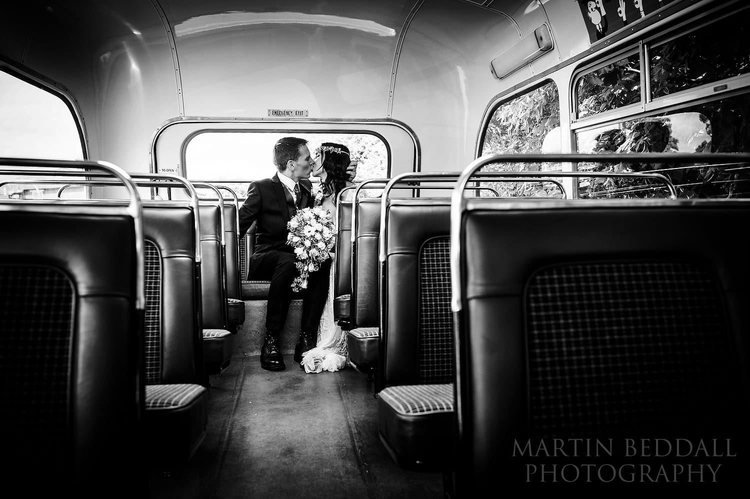 Bride and groom kiss on the vintage wedding bus
