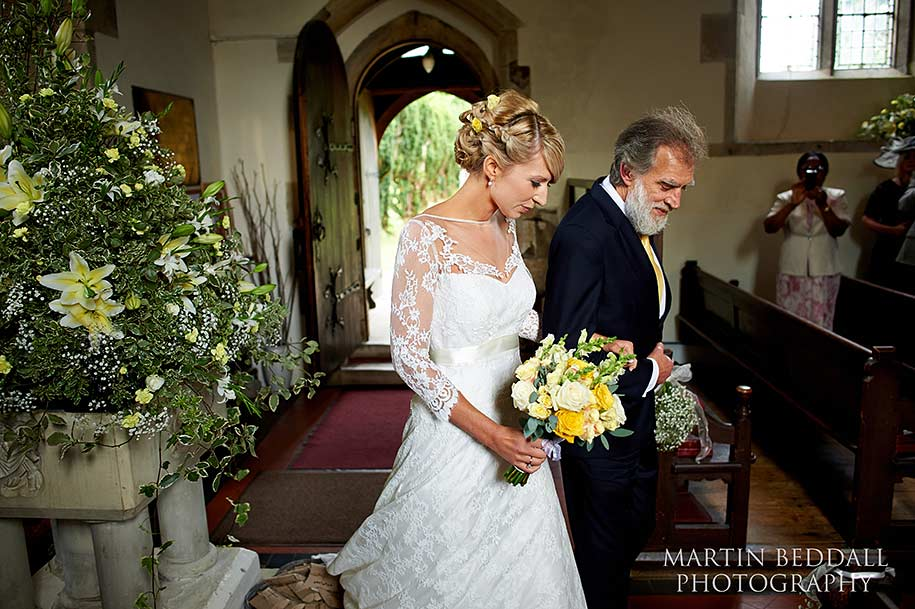 Bride and her father walk down the church aisle