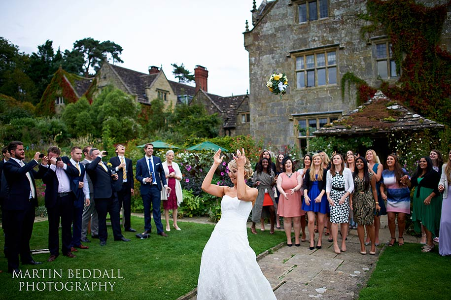 Bride tossing her bouquet at Gravetye Manor