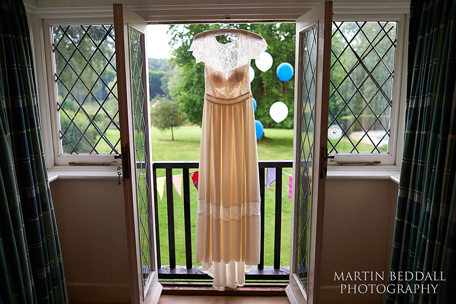 Bride's dress haning on the window