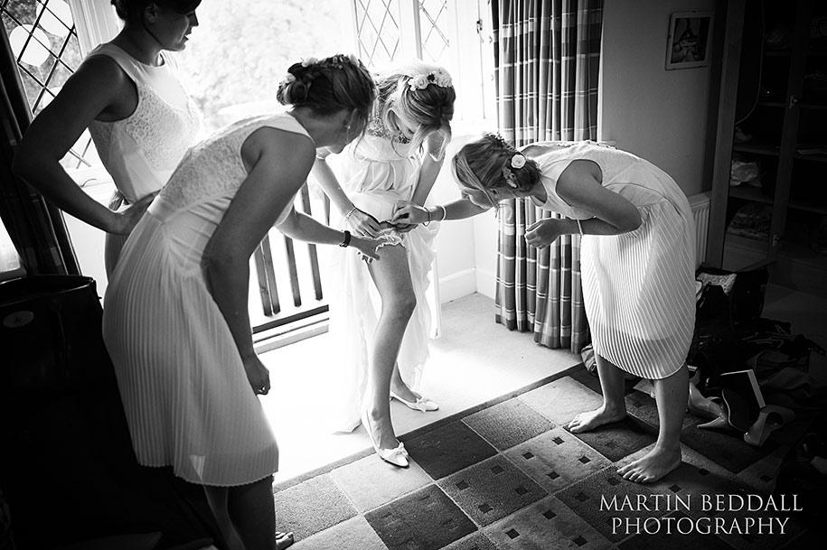 Bridesmaids inspect the bride's garter