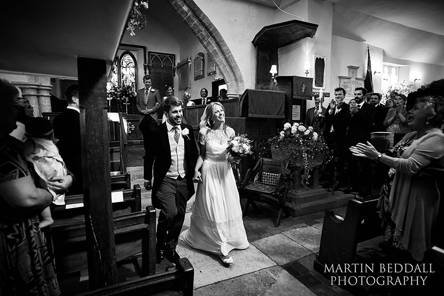 Bride and groom exit All saints church in Minstead Hampshire