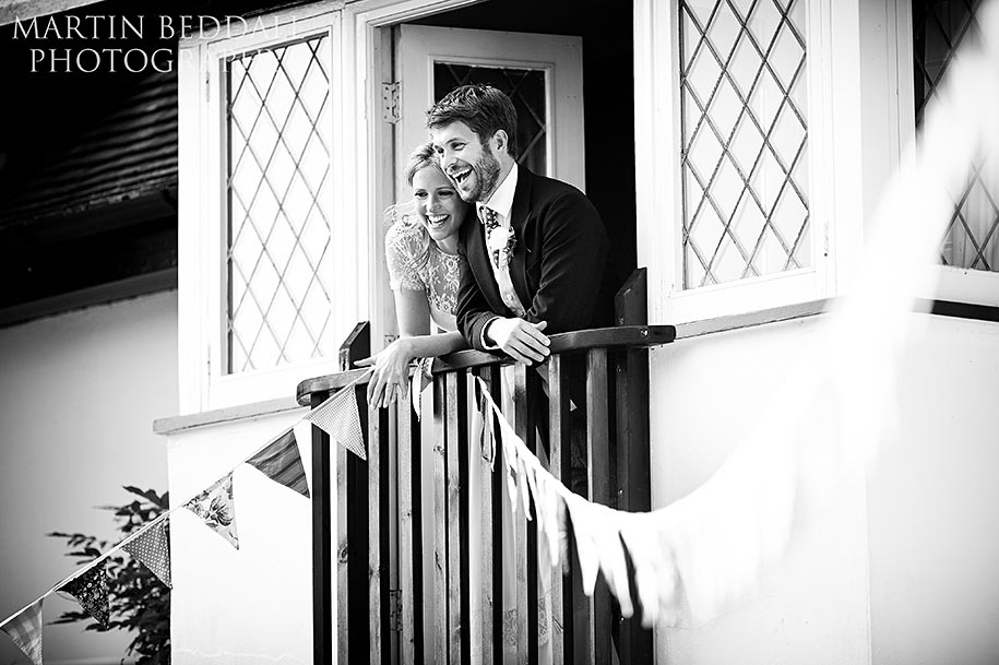 Bride and groom appear at a window