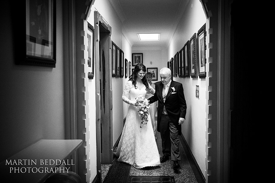 Bride walks with her father to the ceremony in the Great Hall at Northampton Guildhall