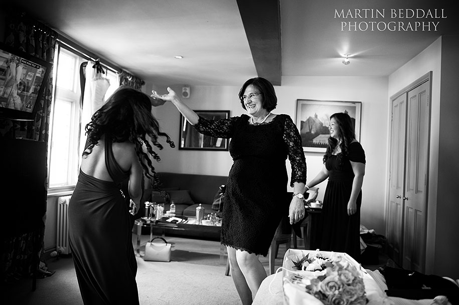 Bride's mother dances with a bridesmaid during preps