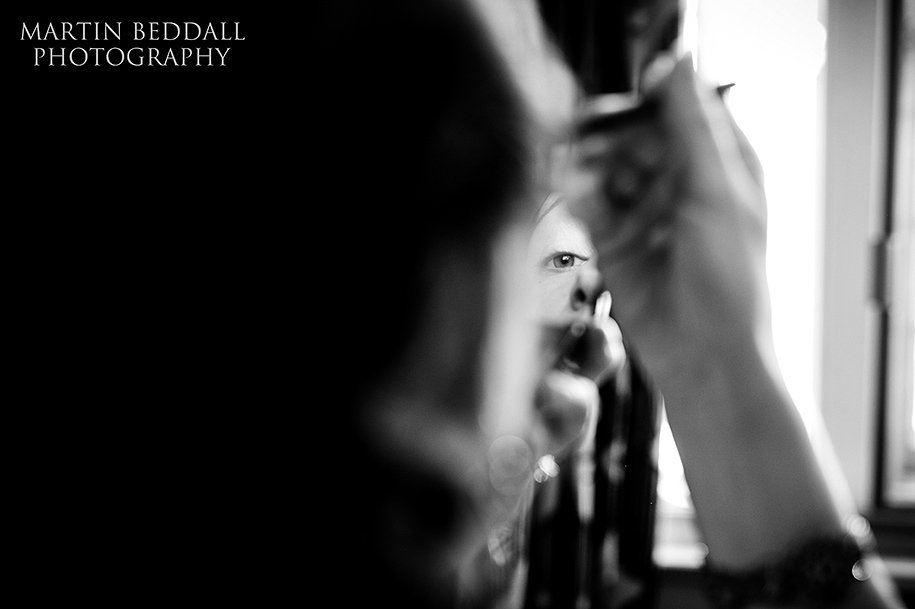 Closeup of bride applying her makeup
