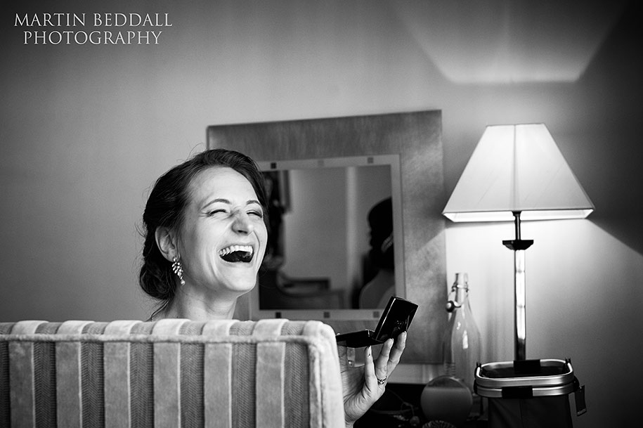 Bride laughs as she does her makeup