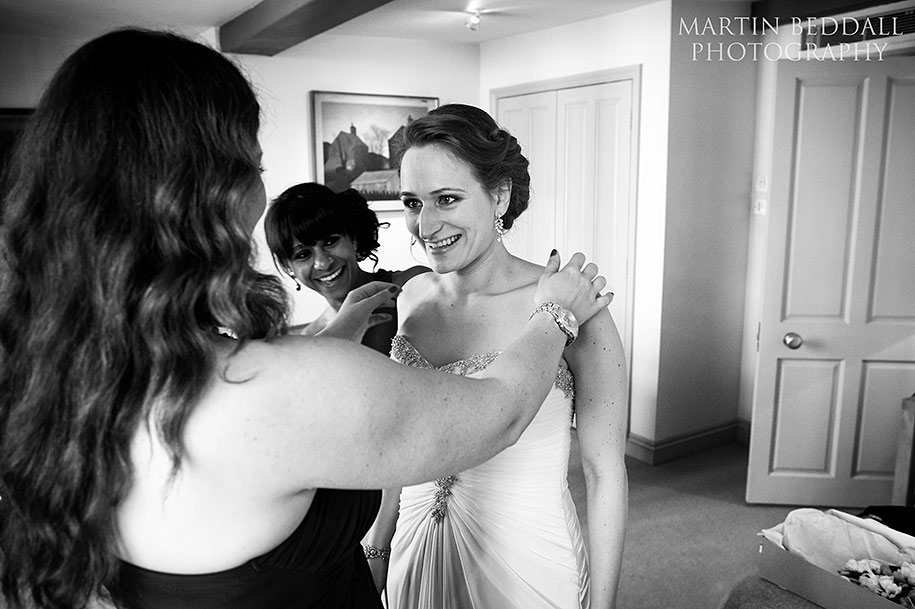 Bridesmiads help the bride into her dress