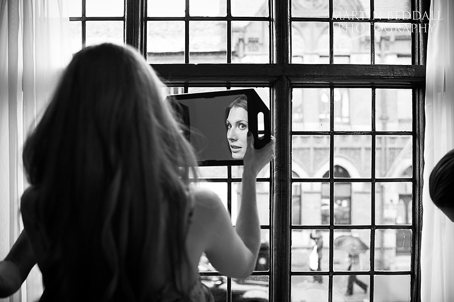 Bride checks her makeup in a mirror