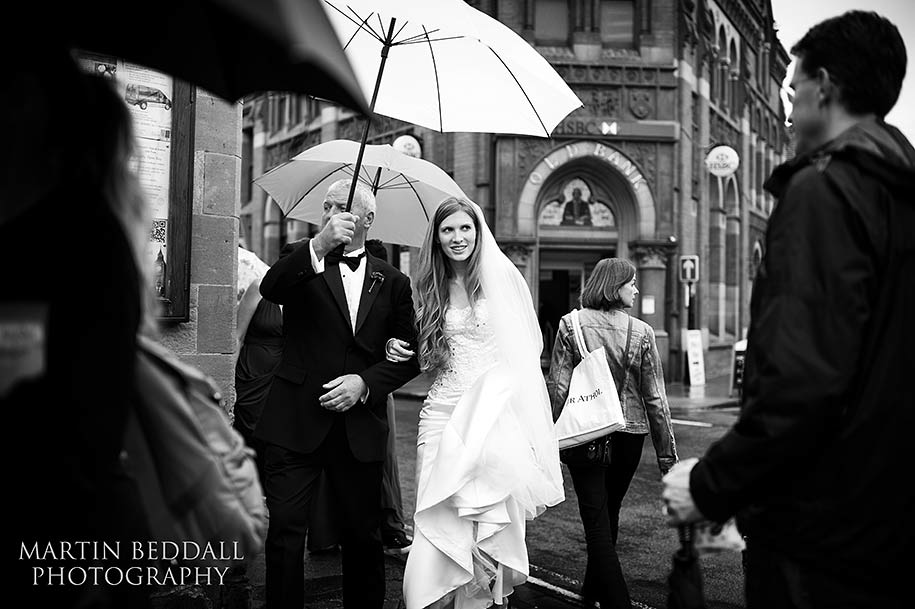 Bride heads to the ceremony in the rain