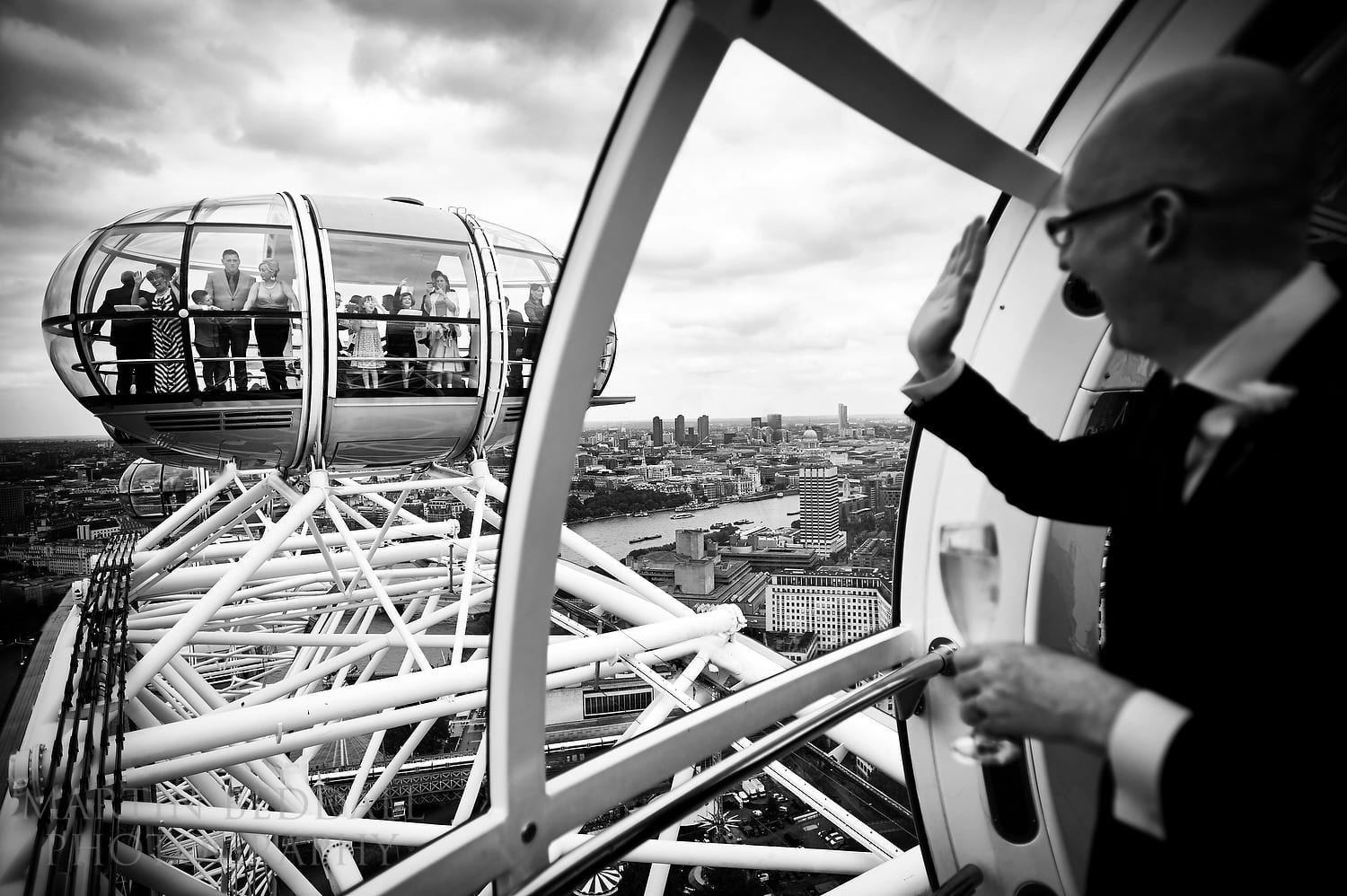 Groom waves to wedding guests in next pod at London Eye wedding