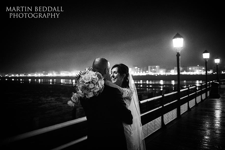 Bride and groom embrace on Worthing Pier at night