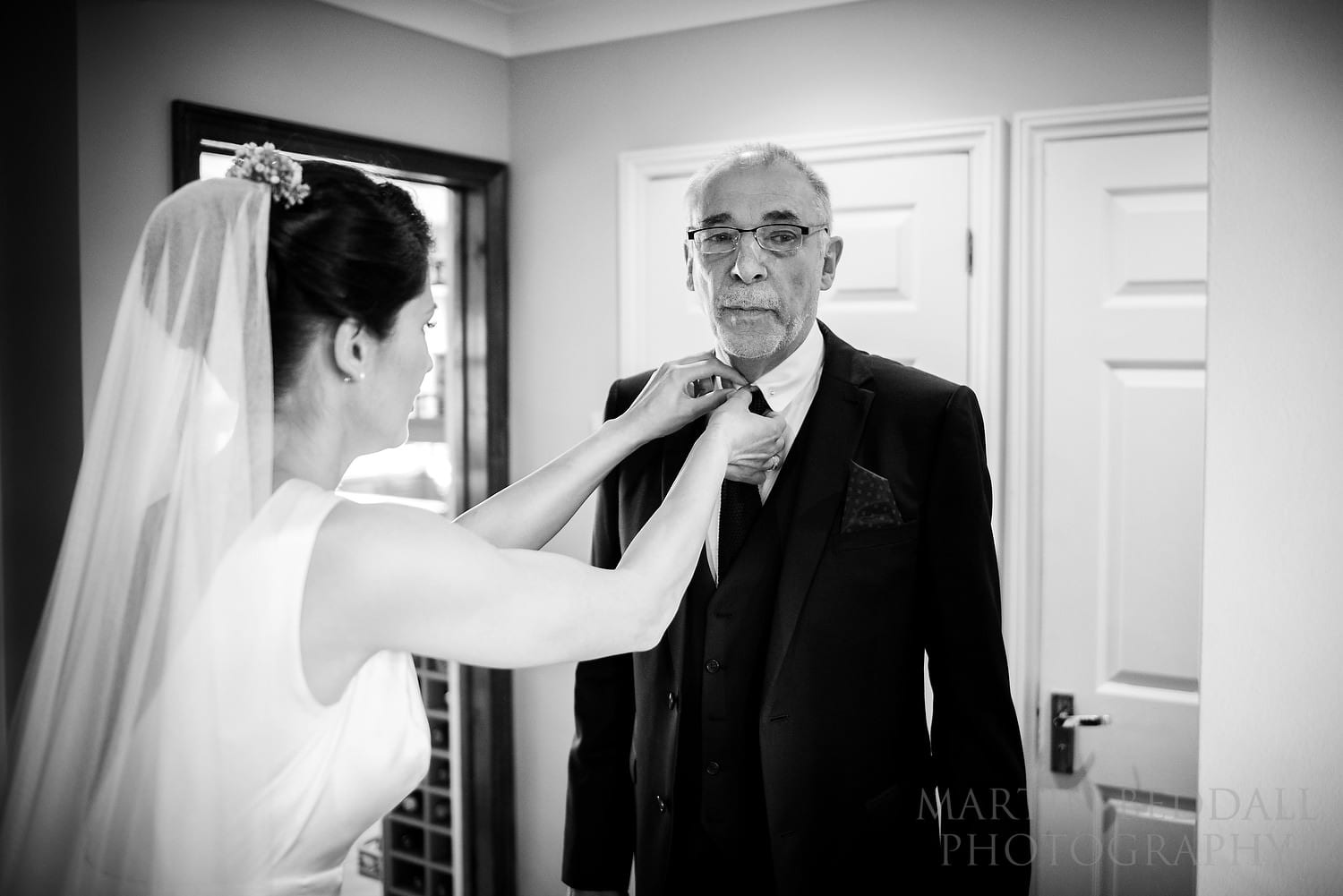 Bride helps her father with his collar