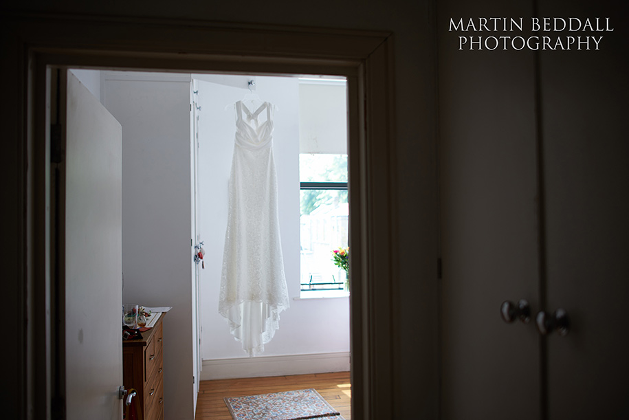 Bride's dress hanging in her bedroom