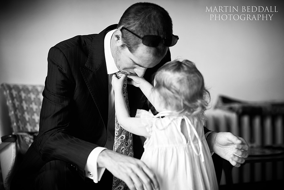 Flowergirl helps her dad with his tie
