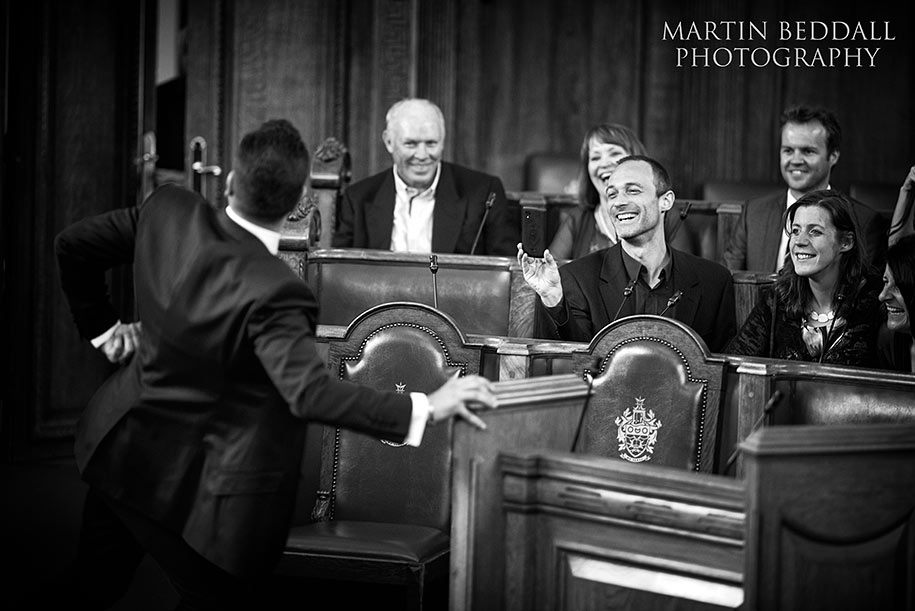 Groom messes around with guest before the wedding ceremony at Islington Town Hall