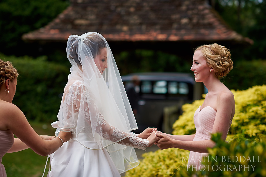 Bride holds hands with her sister before entering the church
