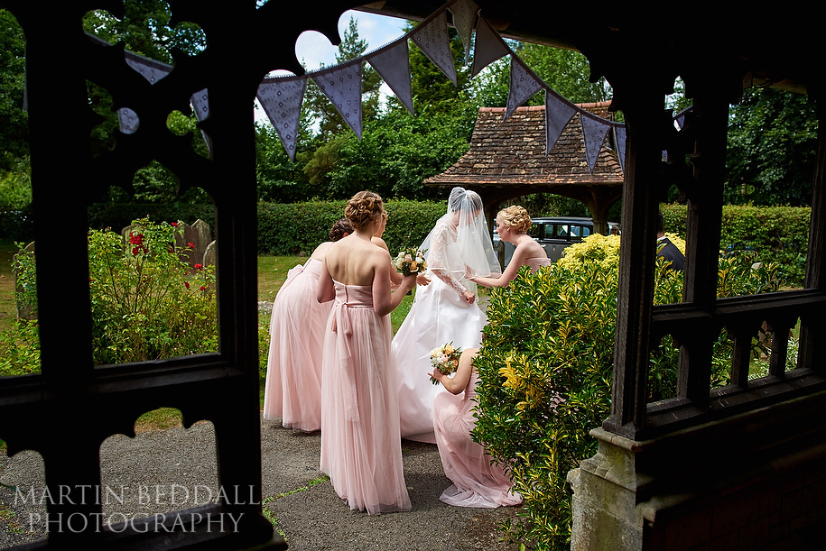 Bridesmaids help get the bride ready oustide the church