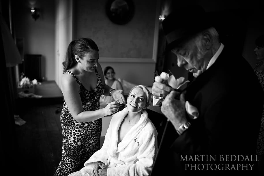 Bride looks on as her grandfather gets ready