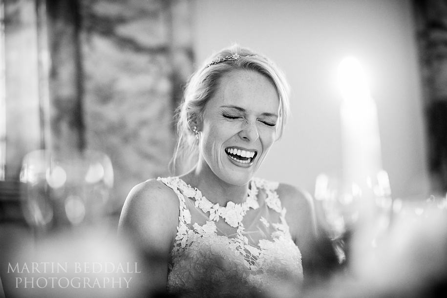 Bride laughing during her mother's speech