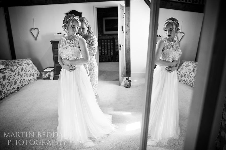 Bride getting into her wedding dress at Caswell House
