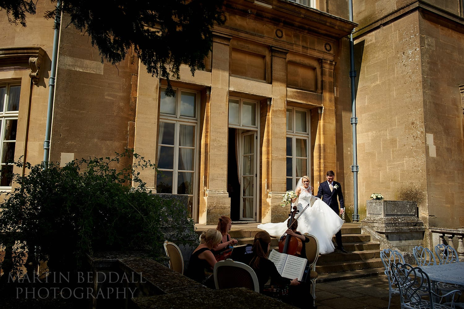 Bride and groom walk out into the gardens at luton Hoo