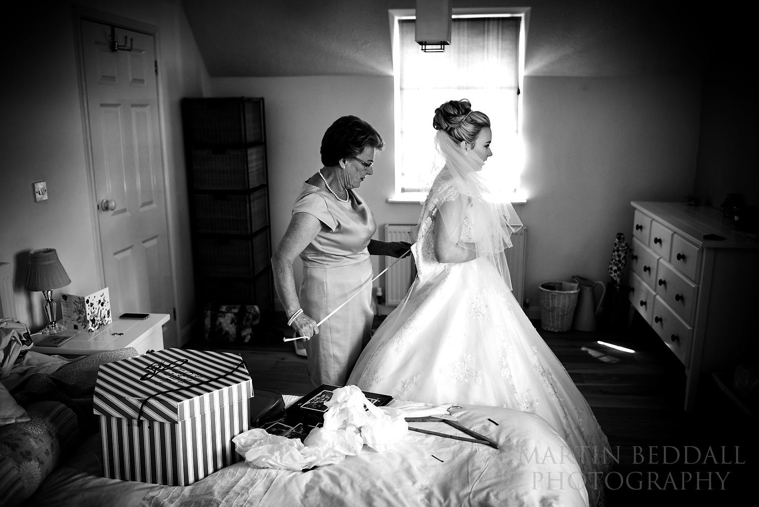 Bride's mother does up the wedding dress