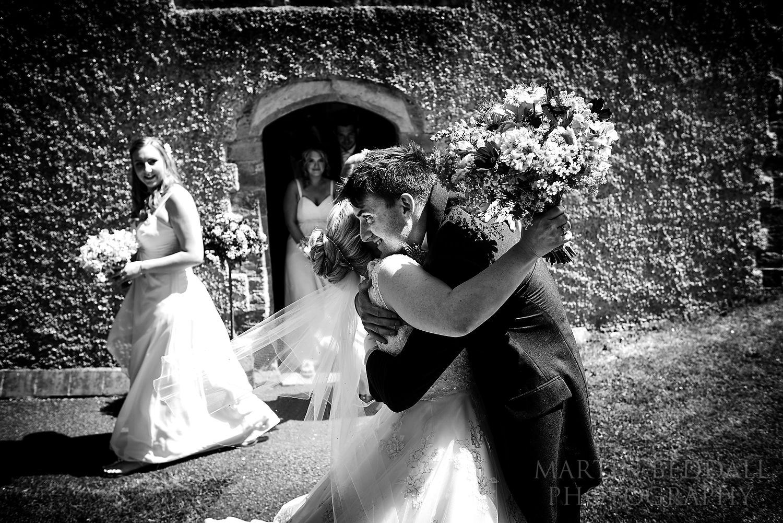 Bride and groom hug outside the church