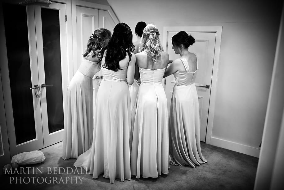 Bridesmaids get the bride into her dress
