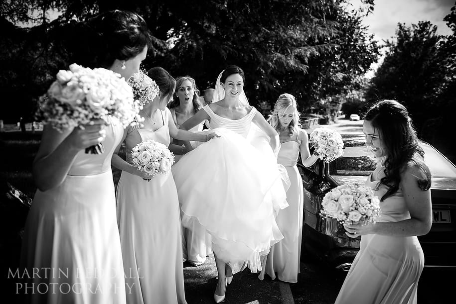 Bride arrives at the church helped by her bridesmaids
