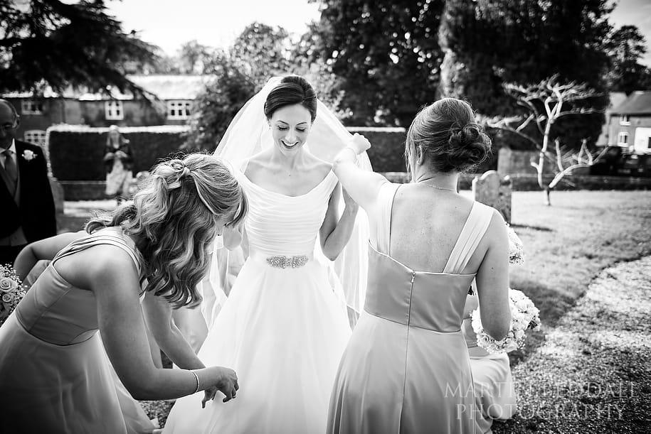 Bridesmiads prepare the bride outside the church