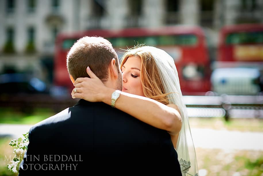 Bride and groom kiss in Berkeley Square London