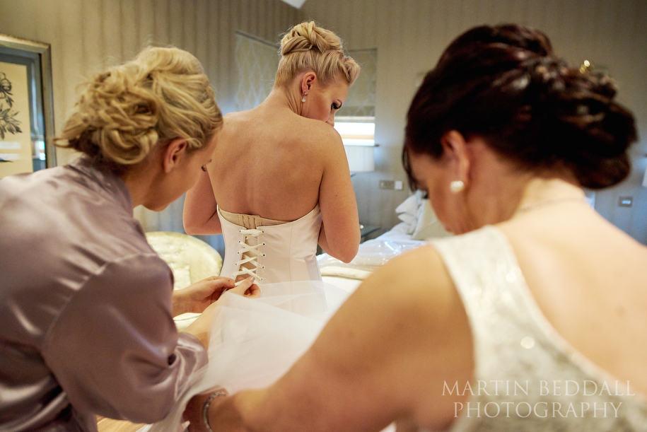 Bride gets into her dress at Hedsor